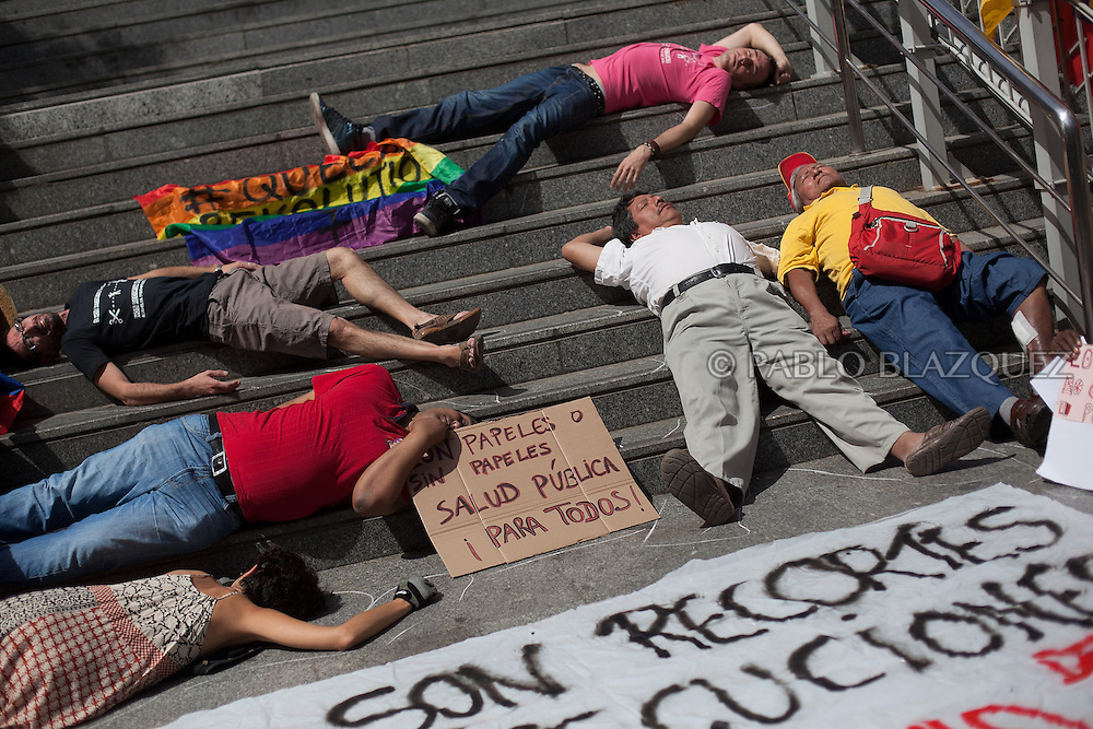 People lay on the ground outside Gregorio Maranon Hospital as they take part in a demonstration against the Spanish government's latest austerity measures concerning medical care for immigrants, in the center of Madrid, on September 1, 2012. Sign reads 'Health care for everyone'.