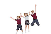 Portrait of happy school children holding hands while jumping over white background