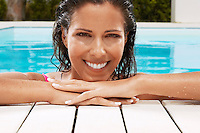Woman in Swimming Pool resting on poolside portrait ground view