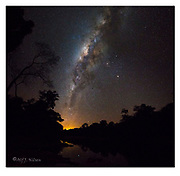 The Milky Way and Rio Cristalino (southern Amazon, Brazil). A mosaic of two images. Nikon D810, 14-24mm @ 14mm, f3.5, 10 sec, ISO3200. The orange glow is the lights from the city of Alta Floresta. Mars and Saturn together with the orange star Antares form the triangle just to the right (west) of the galactic centre.