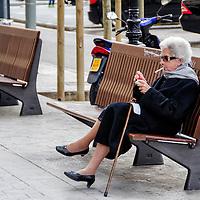 Una mujer de la tercera edad se fuma un cigarrillo en la calle Paseo de Gracia en Barcelona, España. An elderly woman smokes a cigarette on the street Paseo de Gracia in Barcelona, Spain.