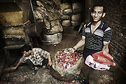 "A young worker ""Zabbeleen"" at a workshop of Mokattam, shows different types of bottles that are crushed and then will classified by different types of plastic . The quarry was originally located where the settlement of Mokattam, is now used for storage of paper and aluminum. On the outskirts of Cairo in the middle of Manshiet Nasr neighborhood is located Mokattam settlement known as ""Garbage City"" is inhabited by Zabbaleen, a community of about 45,000 Coptic Christians living for decades to recycle waste generated by the Egyptian capital: plastic, aluminum, paper and organic waste transformed into compost. Most part of the Association for the Protection of the Environment (APE), an NGO that works in the area, whose objectives are to protect the environment and improve the livelihoods of garbage scavengers in Cairo. According to the UN, the work is done in Mokattam is one of the ten best examples of world environmental improvement. El Cairo , Egypt, June 2011. ( Photo by  Jordi Camí )."