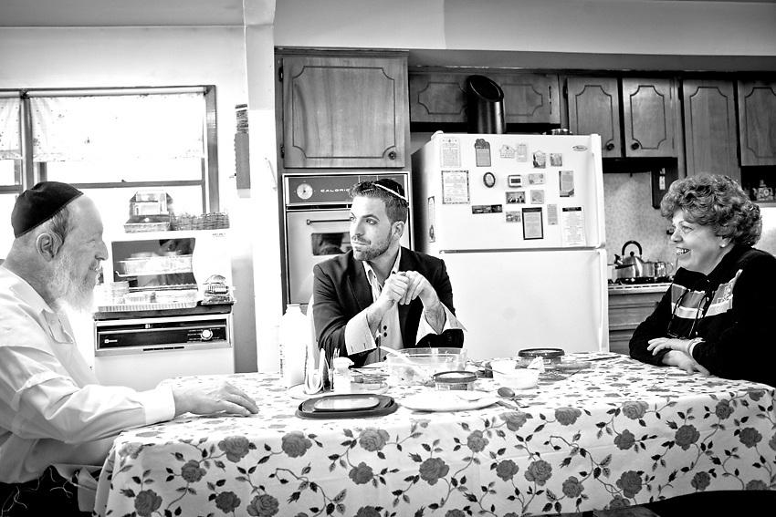 Kal Holczler siede al tavolo con suo padre e sua madre per pranzo. Non ci sono visti per piu` di un anno e, nonostante la vita molto diversa che vivono, riescono a ritagliarsi uno spazio di normalita` nella cucina di un'infanzia passata per Kal e rimasta invece immbile per i suoi genitori che non hanno mai lasciato la comunita` ortodossa di New Square da quando i loro genitori la fondarono subito dopo la liberazione dai campi di sterminio in Ungheria. Foto scattata nel pomeriggio del 9 Marzo 2014.