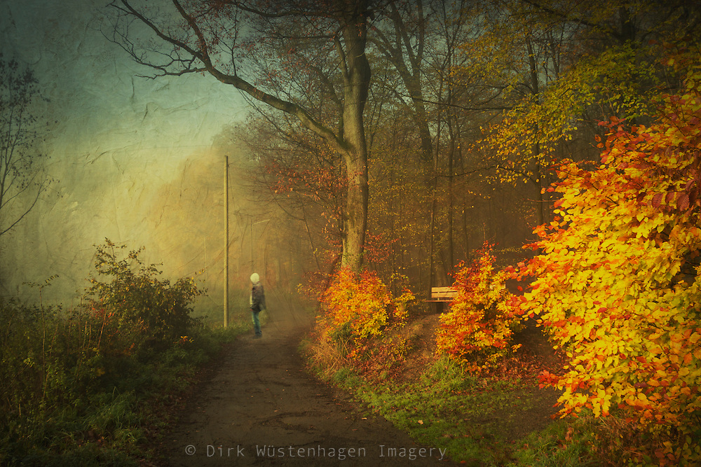 Man standing on a country road at sunrise on a  misty fall morning - textured photograph