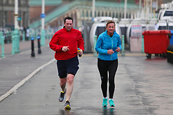 © Licensed to London News Pictures. 17/01/2015. Brighton, UK. People exercising on Brighton Promenade during the occasional rain shower. A very cold day in Brighton and the South Coast with temperatures expected to reach a maximum of 4C down the South Coast. Photo credit : Hugo Michiels/LNP