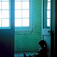 Small child sits alone in the dark , dirty hallway of a rundown apartment building.