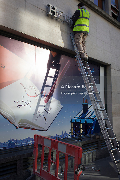 Workman up a ladder installs lettering for the refurbished Hermes store in London's New Bond Street.