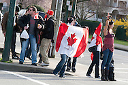 A group of fans cheer and chant at cars as they drive past on a busy intersection<br /> <br /> Tens of thousands of people in Vancouver took to the streets on Sunday 28th February 2010 to celebrate Canada's 3-2 overtime win over the United States for the gold medal in men's Olympic hockey...Traffic came to a halt in and around the downtown of the host city for the Winter Games following the dramatic finish to the match, which featured Sidney Crosby scoring to secure the victory on the final day of Olympic competition.