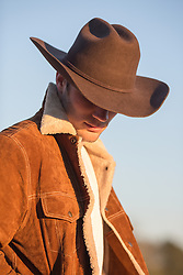 cowboy at sunset with head lowered