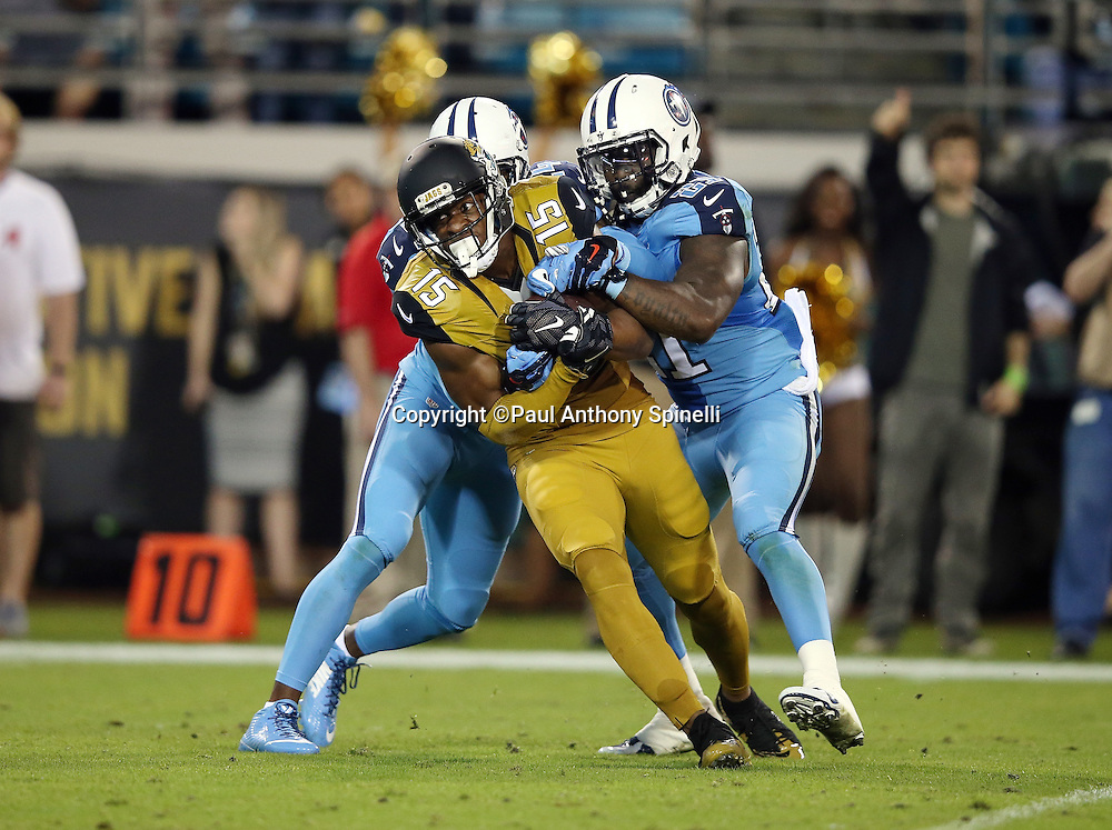 Jacksonville Jaguars wide receiver Allen Robinson (15) catches a 38 yard second quarter pass for a first down at the Tennessee Titans 12 yard line with less than one minute left before halftime as he gets gang tackled by Tennessee Titans cornerback Coty Sensabaugh (24) and Tennessee Titans strong safety Da'Norris Searcy (21) during the 2015 week 11 regular season NFL football game against the Tennessee Titans on Thursday, Nov. 19, 2015 in Jacksonville, Fla. The Jaguars won the game 19-13. (©Paul Anthony Spinelli)