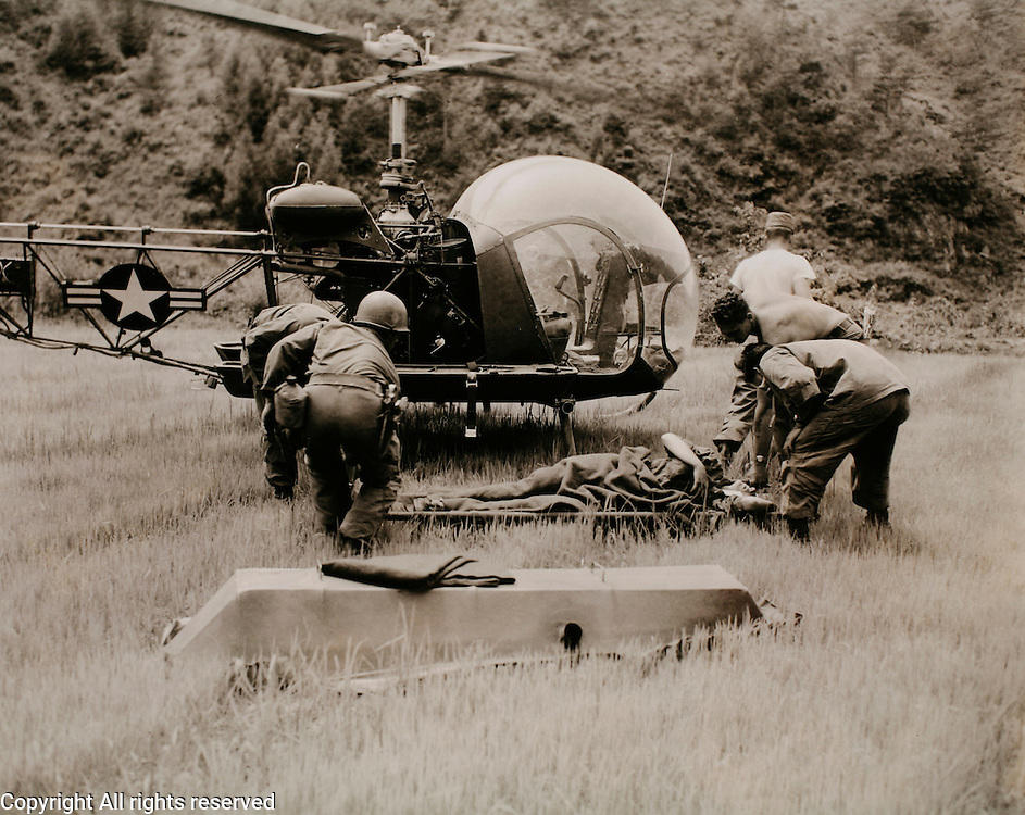 Evacuation for surgical care: ..Near the village of Chup-A-Yang, Korea, a soldier of the 21st Inf. Regiment, 24th U.S. Inf. Div., badly wounded form enemy mortar fire is loaded aboard a helicopter to be flown to the rear for surgical care. ..