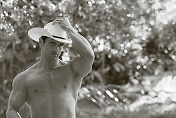 shirtless cowboy holding on to his cowboy hat outdoors