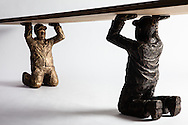 Natanel Gluska's Little Strong Man, part of a furniture system, stackable little brass statues. Pictured here with a hardwood board held up by the statues.