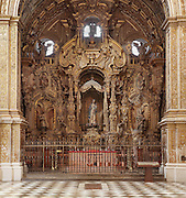 Baroque altarpiece, 18th century, in the Capilla de Nuestra Senora La Antigua, in Granada Cathedral, or the Cathedral of the Incarnation, built 16th and 17th centuries in Renaissance style with Baroque elements, Granada, Andalusia, Southern Spain. In the centre of the altarpiece is a statue of the Virgin and child under a canopy, and to either side, San Cecilio and San Gregorio Betico. Several architects worked on the cathedral, which, unusually, has 5 naves and a circular capilla mayor instead of an apse. Granada was listed as a UNESCO World Heritage Site in 1984. Picture by Manuel Cohen