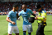 Fernandinho (25) of Manchester City trys to stop Sergio Aguero (10) of Manchester City confronting a police officer who was keeping him away from the celebrating crowd after Raheem Sterling (7) of Manchester City winning goalduring the Premier League match between Bournemouth and Manchester City at the Vitality Stadium, Bournemouth, England on 26 August 2017. Photo by Graham Hunt.