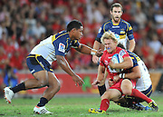 """Sam Lane is caught in the tackle of Andrew Smith with Ita Vaea approaching from the left in the Super 15 Rugby Union match (Round 7) between the Queensland Reds and the ACT Brumbies played at Suncorp Stadium (Brisbane, Australia) on Good Friday 6th April 2012 ~ Queensland (20) defeated the Brumbies (13) ~ This image is intended for Editorial use only - Required Images Credit """"Steven Hight - Aura Images"""""""