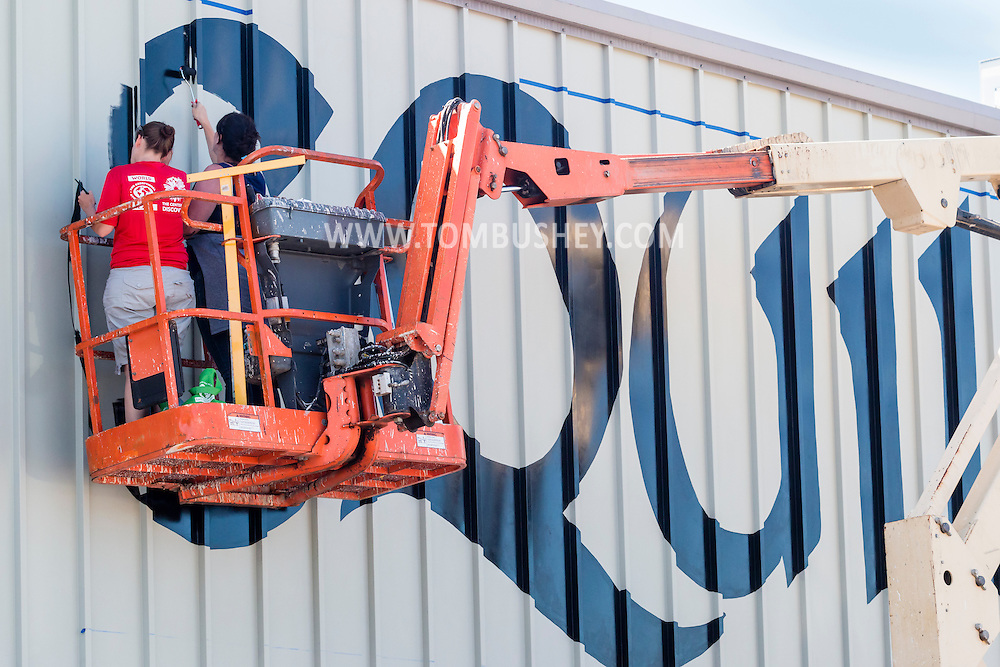 "Middletown, New York - Painters in a lift fill in the ""e"" on the Equilibrium sign at Equilibrium Brewery on Aug. 23, 2016."
