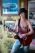 """Musician, Sarah Burrill, 57, is photographed in her home in Eastham, MA. She was diagnosed with stage 4 inflammatory breast cancer at the age of 40.  """"I was in shock when I found out and did everything under the sun. I had two rounds of high dose chemotherapy and a mastectomy; I did herbs and glyconutrients; I even had myself energetically erased!"""" she exclaims. Sarah got an enormous amount of support from her community which hosted six fundraisers for her. """"I'd go out just for hugs and to have connection with people even though I looked quite scary,"""" she recalls. Sarah eventually had her other breast removed because she didn't want to have reconstructive surgery and was tired of medical procedures. """"I did mourn both of them but it's okay at this point,"""" she says. The tattoos she now has on her chest represent her connection to her sister, whose ashes are buried under the cherry tree in her yard and her mother, whose ashes are buried under the dogwood. """"Music really helped sustain me when I was going through treatment,"""" Sarah explains. """"I brought my guitar to the hospital and when I was too sick, I watched the Beatles anthology videos"""".  Sarah wrote the song """"Rise Above""""--from which this project's title comes--for the Cape Cod Women's Music Festival a few years ago. The lyrics became a local anthem for women going through breast cancer. """"So put your hands in our hands, we'll walk together strong and we'll kick some ass, we'll rise above and we'll carry-on,"""" she sings."""