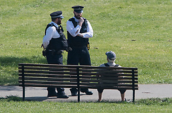 © Licensed to London News Pictures. 11/04/2020. London, UK. Police officers talk to a man sat on. A park bench in Primrose Hill, London over Easter Bank holiday weekend, during a pandemic outbreak of the Coronavirus COVID-19 disease. The public have been told they can only leave their homes when absolutely essential, in an attempt to fight the spread of coronavirus COVID-19 disease. Photo credit: Ben Cawthra/LNP