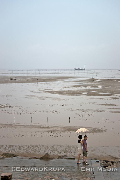 Couple in the drizzling rain at low tide by the South China Sea.