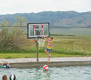 Little boy dunking basket ball during family fun at Durfee Hot Springs in Almo, Idaho near Castle Rock State Park and the City of Rocks National Reserve. MR