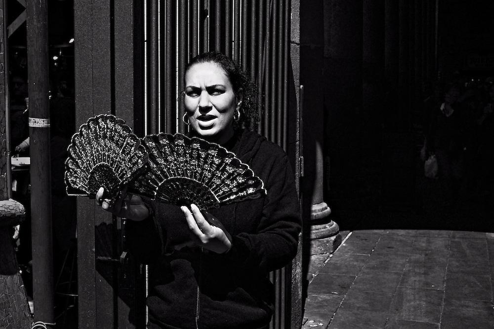 Woman selling fans inside La Boqueria market