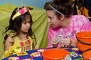 Middletown, New York  - A teenage girl helps a young girl with stickers during the Halloween Fall Festival at the Middletown YMCA Center for Youth Programs on Oct. 26, 2013.
