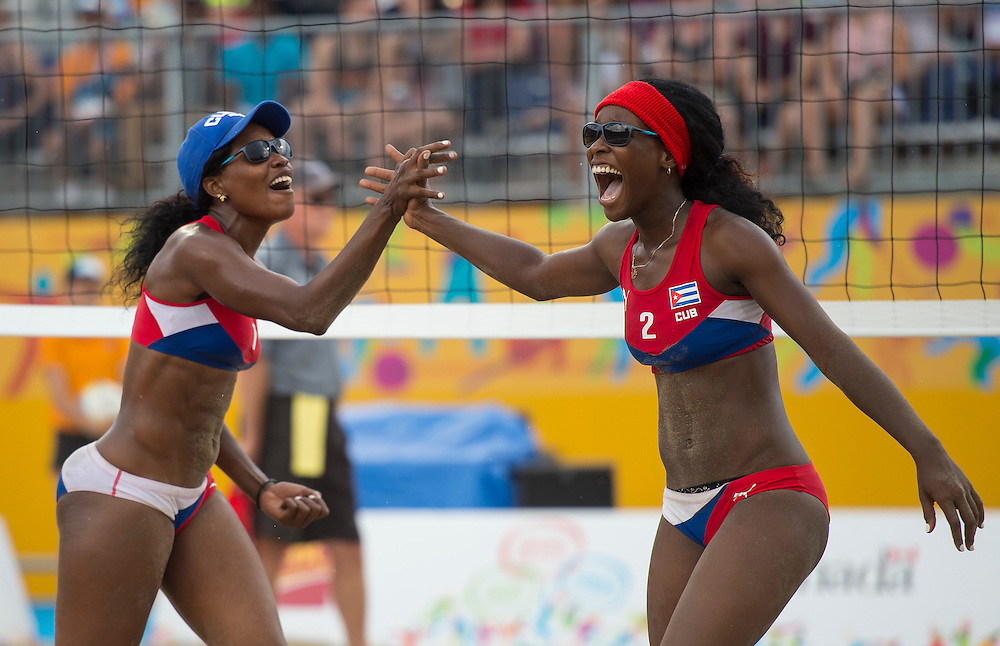 Lianma Flores (left) and Leila Martinez (right #2) of Cuba celebrate their victory during Canada vs. Cuba in beach volleyball competition at the 2015 PanAm Games in Toronto.