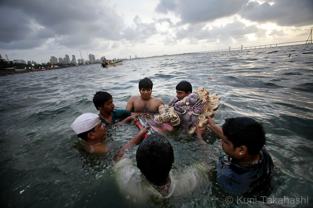 Hindu devotees immerse ganesha idols into the sea in Mumbai, India on Sep 16, 2010 on the 6th day of Ganpati festival. The 10-day hindu festival, celebrating the birthday of Lord Ganesha who is widely worshiped as the god of wisdom, prosperity and good fortune, attracts tens of thousands people..Photo by Kuni Takahashi