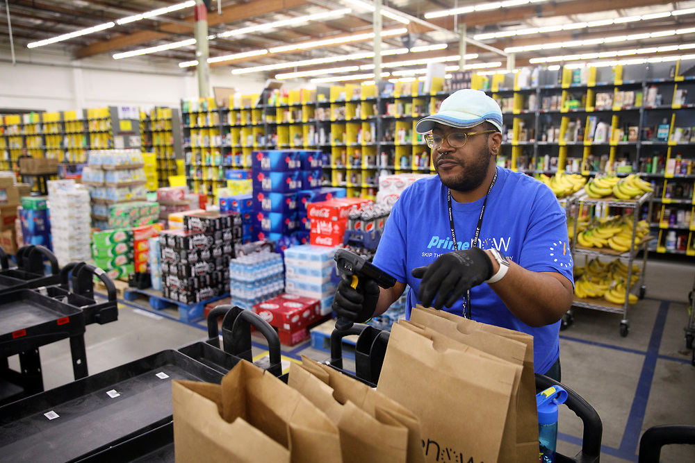 Ryan White, Amazon associate, fills shopping bags with products for customers orders at the Amazon.com Inc. Prime Now fulfillment center warehouse on Monday, March 27, 2017 in Los Angeles, Calif. The warehouse can fulfill one and two hour delivery to customers. Complex supply chains such as Amazon's and e-commerce trends will impact city infrastructure and how things move through cities. © 2017 Patrick T. Fallon