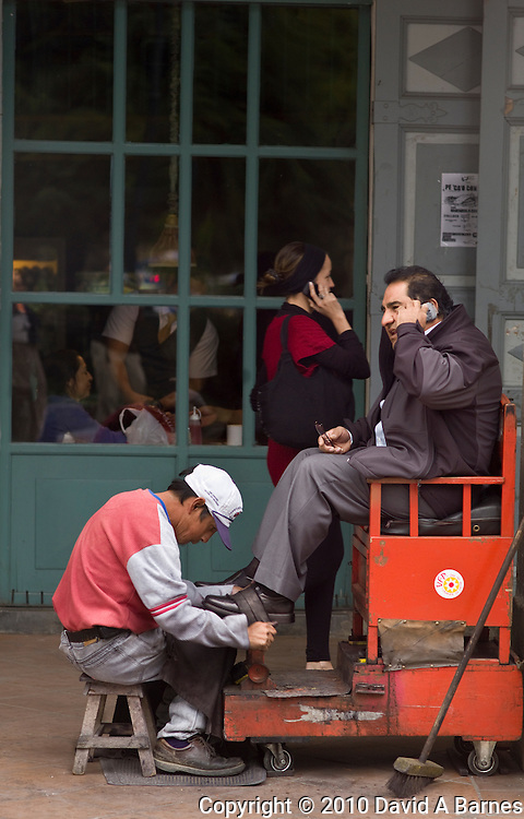 Shoe shine polishing mans shoes while he speaks on cell phone, a woman is on a cell phone in background, Cuenca, Ecuador