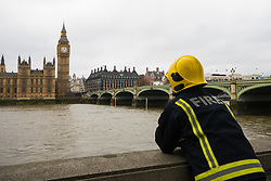 Westminster, London, March 29th 2017. One week after the terror attack on Westminster bridge, it is once again the scene of an emergency services operation as police, ambulance and fire crews search the river after a person jumped from the bridge. The person has not so far been recovered.<br /> PICTURED:  A firefighter scans the river.<br /> CREDIT: ©Paul Davey<br /> FOR LICENCING CONTACT: Paul Davey +44 (0) 7966 016 296 paul@pauldaveycreative.co.uk