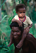 Amuloke Walelo, a Dani tribeswoman from Soroba village in the Baliem Highlands of central Irian Jaya, Indonesia with one of her children on her shoulders as she goes about her daily chores. Image from the book project Man Eating Bugs: The Art and Science of Eating Insects.