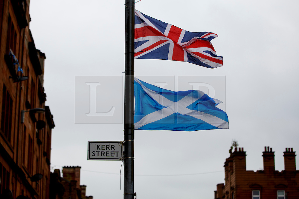 © Licensed to London News Pictures. 18/09/2014. Glasgow, UK. Union jack flag and Scottish Saltire flag are seen in Bridgeton, a unionist area of Glasgow, whilst  people of Scotland going to polling stations to vote on the Scottish independence referendum on Thursday, 18 September 2014. Photo credit : Tolga Akmen/LNP