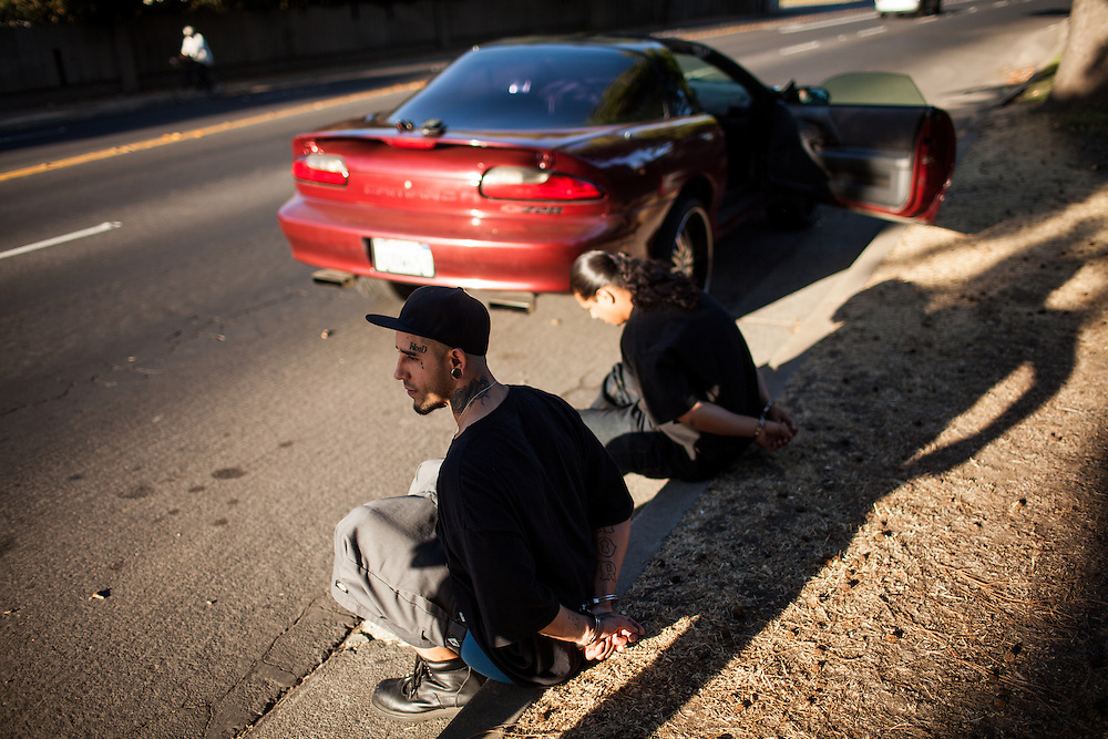 A white power gang member, left, and a friend are detained during a traffic stop by the Community Response Team in Stockton, California September 18, 2013 which targets violent gangs.  Facing stark and rising homicide rates, the California cities Oakland and Stockton are taking a second chance at a novel method of disrupting street gangs, called Ceasefire, in which the police use social-analytics software to map out connections between a city's most violent gang members, using the data to make targeted and coordinated arrests.
