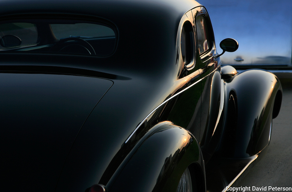 The smooth silky lines of a vintage, 1938 Chevy Coop, owned by John Boyce, from Omaha, Nebraska, soaks up the last rays of sunshine as it sits in front of a diner in Pleasant Hill, Iowa, a suburb of Des Moines....  The cars and their owners were in Des Moines over the 4th of July weekend for the Good Guys 16th Heartland Nationals held at the Iowa State Fairgrounds, bringing over 3,500 of the country?s hottest rods and coolest customs to Iowa?s Capital City.  This coop was voted Car of the Year at the 2006 event...Exhibitors are very skilled, multi-talented craftsmen. They dedicate thousands of hours to bring their hot rod or custom  autos to a high standard. Unlike many car shows the Good Guys usually drive both to and from the event...Photo by David Peterson..