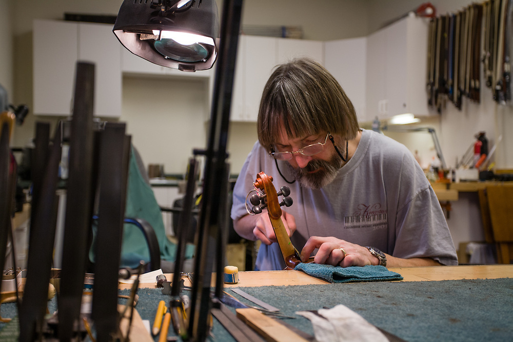 Stephen Beekman resetting the neck of a violin in his shop in Peace Dale, Rhode Island.