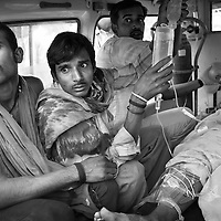 The husband (2nd left) of a 30-year old woman who had attempted suicide looks on anxiously as she is transported by ambulance from the JSS hospital in Ganiyari to the ICU at the large government hospital in Bilaspur, 25km away. The woman is one of many such cases of attempted suicide by the ingestion of insecticide. She was brought to the JSS hospital on a motorbike where doctors spent two hours stabilising her. The woman survived thanks to the efforts of the JSS and was discharged from hospital one week later. The JSS (Jan Swasthya Sahyog or People's Health Support Group) is a public-health initiative established in 1996 by a handful of committed doctors, all of whom trained at elite medical schools in India. While many of their peers secured high profile, high earning posts in premier hospitals in India, the US and the UK, the doctors at JSS provide a service for poor and marginalised rural communities in Bilaspur district in the eastern India.<br />