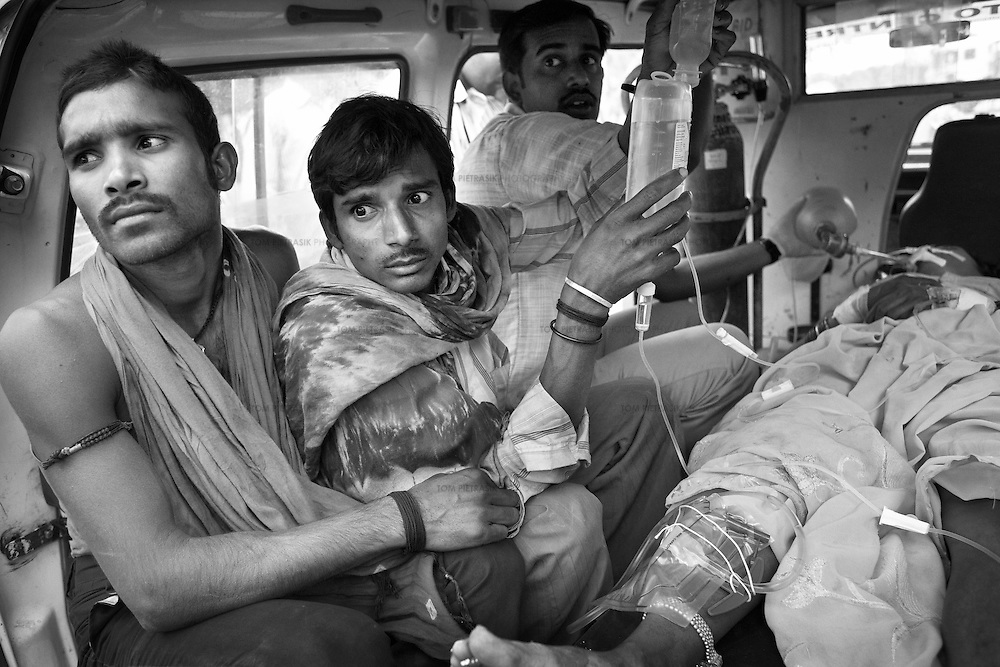 The husband (2nd left) of a 30-year old woman who had attempted suicide looks on anxiously as she is transported by ambulance from the JSS hospital in Ganiyari to the ICU at the large government hospital in Bilaspur, 25km away. The woman is one of many such cases of attempted suicide by the ingestion of insecticide. She was brought to the JSS hospital on a motorbike where doctors spent two hours stabilising her. The woman survived thanks to the efforts of the JSS and was discharged from hospital one week later. The JSS (Jan Swasthya Sahyog or People's Health Support Group) is a public-health initiative established in 1996 by a handful of committed doctors, all of whom trained at elite medical schools in India. While many of their peers secured high profile, high earning posts in premier hospitals in India, the US and the UK, the doctors at JSS provide a service for poor and marginalised rural communities in Bilaspur district in the eastern India.<br /> <br /> The JSS operate out of a hospital in Ganiyari, near Bilaspur. Relying on grants and donations, the JSS provide a first-class service for a community that would otherwise rely on underfunded and poorly resourced government facilities. Though JSS hospital boasts 30 beds, two operating theatres, a fully-equipped lab and three outpatient clinics a week, the service provided by JSS is over-subscribed by a community of 800,000 people from 1,500 villages. <br /> <br /> To address the malnutrition, the JSS offers training on new agricultural techniques. The JSS has a well established outreach program of village-clinics and employs over 100 village health workers serving 53 villages. They also operate an ambulance service and assist with transport costs for a community who's access to essential services has been undermined by the Chhattisgarh government's decision to completely disinvest in public transport. <br /> <br /> Photo: Tom Pietrasik<br /> Chhattisgarh, India. <br /> March 2010