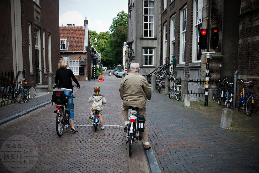 Fietsers wachten keurig voor het rode verkeerslicht.<br /> <br /> Three generations of cyclists are waiting at a traffic light