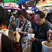 A group of Chinese middle aged friends eat their dinner in the street, food from the nearby food stall in Times Square. 7 million people live on 1,104km square, making it Hong Kong the most vertical city in the world.