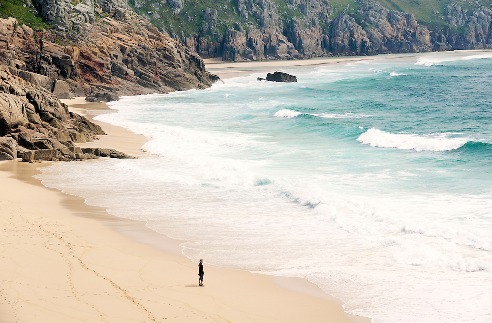 Young woman standing walking alone looking at sea waves on the white sandy beach at Porthcurno Bay in Cornwall, England, UK.