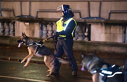 © Licensed to London News Pictures. 05/11/2015. London, UK. Police with dogs at An anti-capitalist  protest organised by the group Anonymous outside Parliament in Westminster on bonfire night 05, November 2015. Bonfire night, also known as Guy Fawkes night, is an annual commemoration of when Guy Fawkes, a member of the Gunpowder Plot, was arrested for attempting to blow up the House of Lords at parliament.   Photo credit: Ben Cawthra/LNP