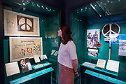 UNITED KINGDOM, London: 21 March 2017 A member of staff at The Imperial War Museum stands in front of an original sketch of the world famous nuclear disarmament symbol by designer Gerald Holtom. It forms part of the 'People Power: Fighting for Peace' exhibition at the Imperial War Museum which explores the evolution of the anti-war movement from the First World War to the present day. Rick Findler / Story Picture Agency