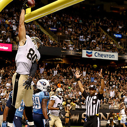 Aug 15, 2014; New Orleans, LA, USA; New Orleans Saints tight end Jimmy Graham (80) dunks after scoring a touchdown against the Tennessee Titans during a preseason game at Mercedes-Benz Superdome. Mandatory Credit: Derick E. Hingle-USA TODAY Sports