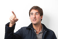 Young shocked man gesturing against white background