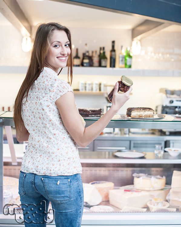 Rear view of smiling woman holding chocolate jar in front of display cabinet at cafe