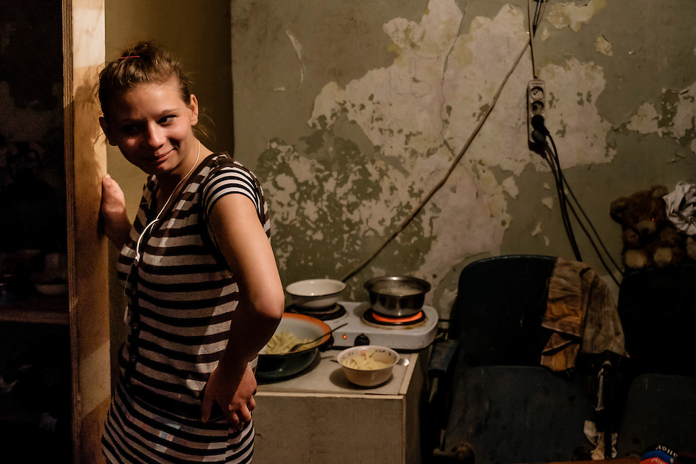 12 of April 2015 / Petrovski/ Donetsk Oblast/ Ukraine - Marina preparing the dinner, pasta  for her four kids, in a small room reserve for cooking. Like most of the family we saw, no husband is present.