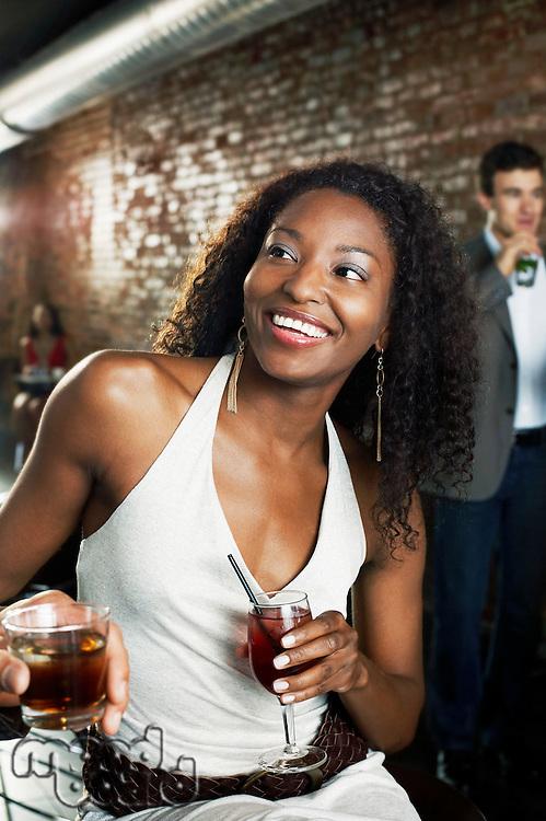 Woman holding cocktail sitting in bar