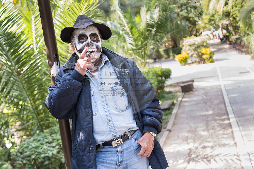 A man dressed as hobo skeleton during the Day of the Dead in the Parque Juarez October 30, 2016 in San Miguel de Allende, Guanajuato, Mexico. The week-long celebration is a time when Mexicans welcome the dead back to earth for a visit and celebrate life.